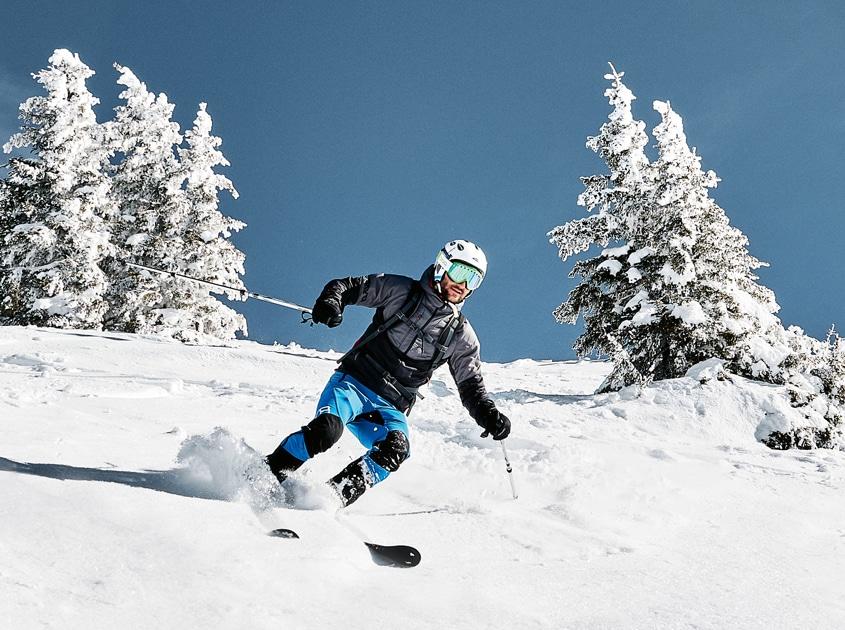 Ein Skifahrer fährt die Piste hinunter