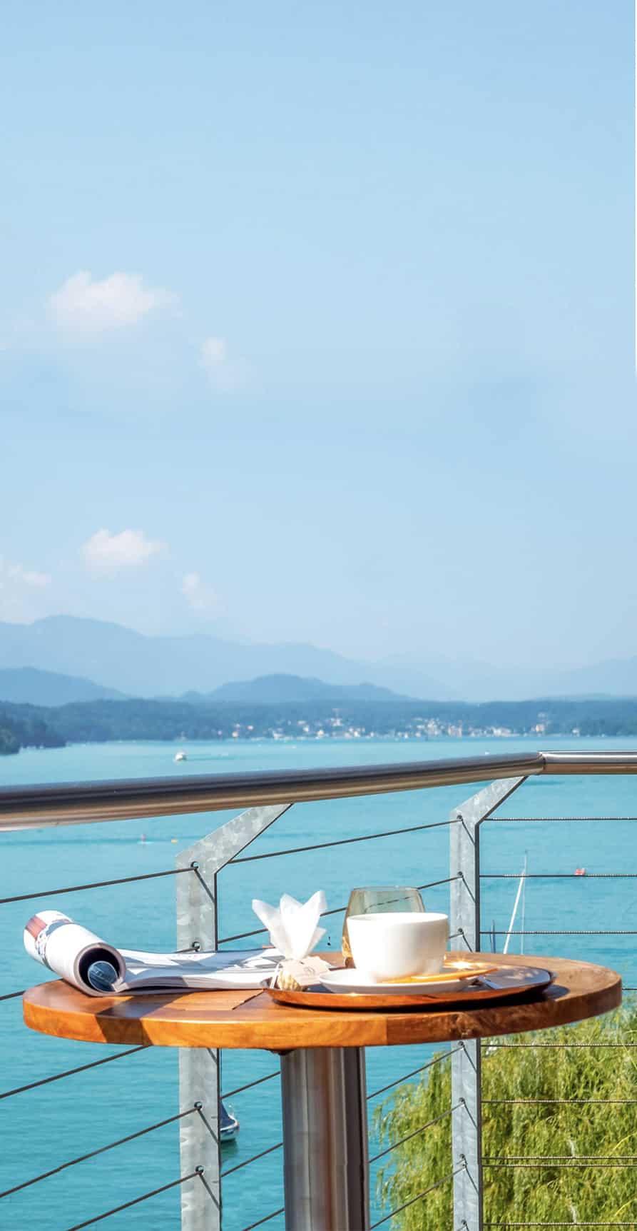 Balkon mit Tisch und Blick auf den Wörthersee